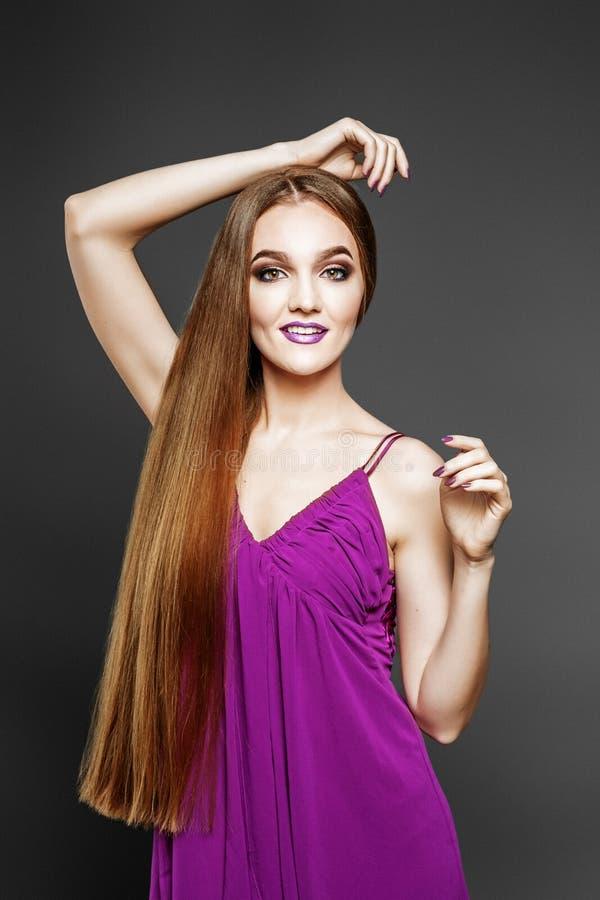 Молодая элегантная девушка в фиолетовом платье ногти красотки nailfile полируя салон Очень длинные волосы стоковая фотография