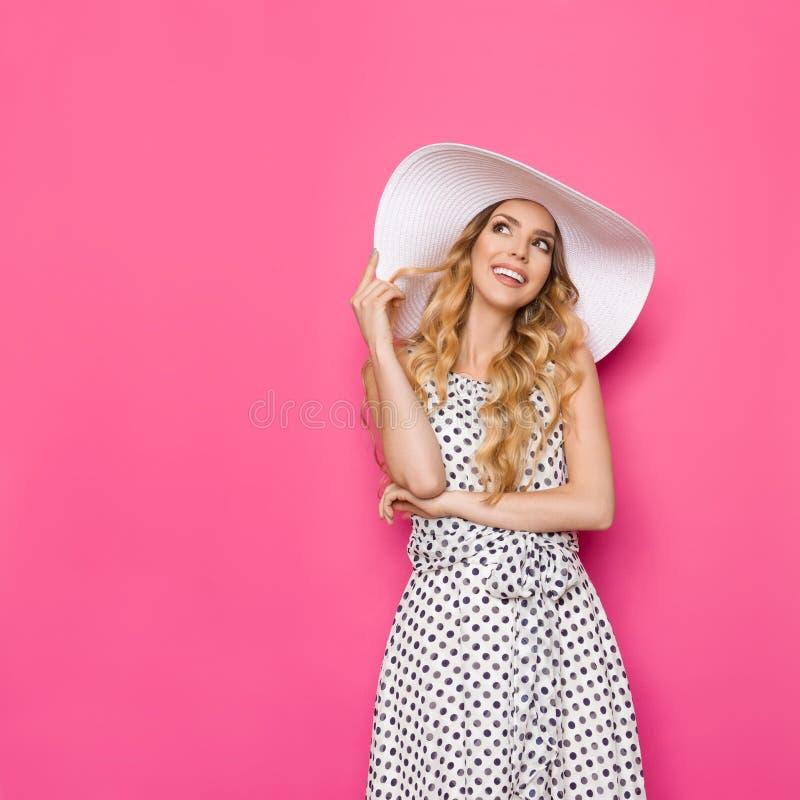 Молодая элегантная женщина в белой шляпе Солнця смотрит вверх и усмехаться стоковая фотография rf