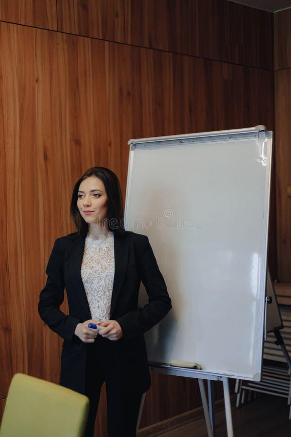 Молодая эмоциональная привлекательная девушка в одеждах дел-стиля работая с flipchart в современных офисе или аудитории стоковое фото