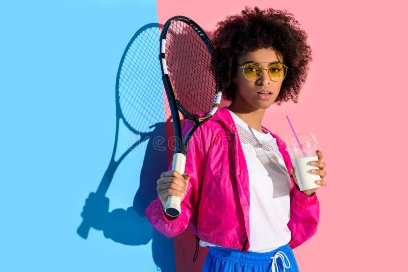 Молодая яркая Афро-американская девушка держа ракетку тенниса и чашку пластмассы с питьем на пинке и сини стоковая фотография rf