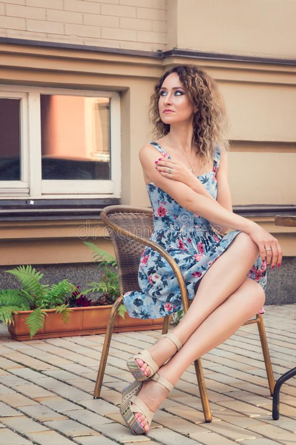 Молодая leggy женщина сидя в кафе улицы плетеного стула Она смотрит к ее праву, ждать кто-то Носить голубое флористическое платье стоковые изображения rf