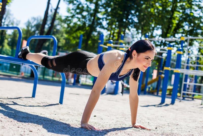 Молодая sportive девушка делать нажимает поднимает стоковое фото