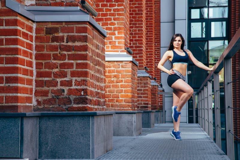 Молодая sporty женщина делая протягивая тренировку в городе стоковое изображение rf