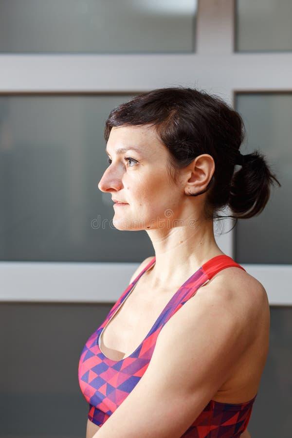 Молодая sporty женщина делая тренировку Sukhasana стоковая фотография