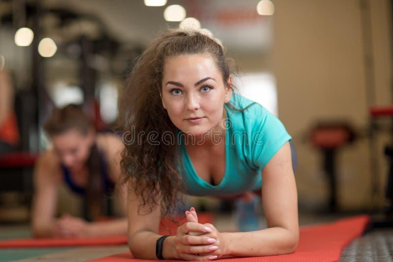 Молодая sporty тренировка женщины на циновках в спортзале стоковое фото