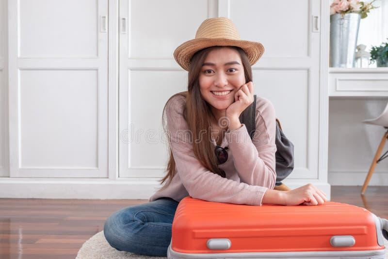 Молодое азиатское вещество упаковки путешественника женщины в оранжевом приготовлении уроков чемодана стоковая фотография