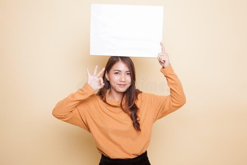Молодое азиатское О'КЕЙ выставки женщины с белым пустым знаком стоковое фото rf
