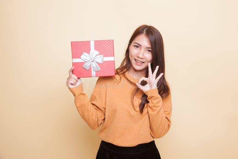 Молодое азиатское О'КЕЙ выставки женщины с подарочной коробкой стоковые изображения