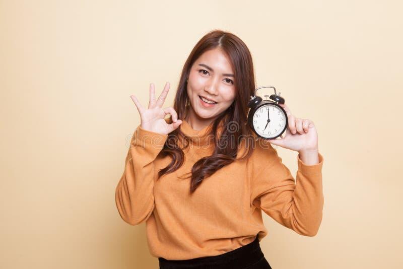 Молодое азиатское О'КЕЙ выставки женщины с часами стоковое фото