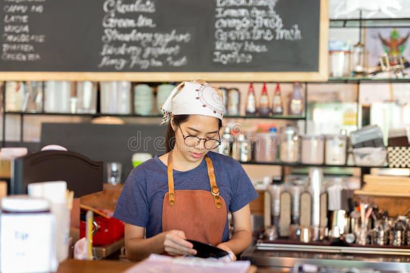 Молодое азиатское barista обтирая плиту с салфеткой в кафе стоковые фотографии rf