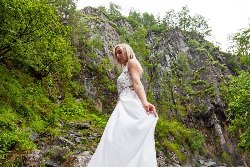 Молодое белокурое положение девушки в руке полу-поворота выправляет платье будуара в горах против водопада и камни любят стоковая фотография rf