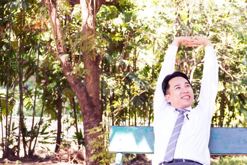Молодое взрослое усаживание бизнесмена и ослаблять в парке Протягивать стоковая фотография rf
