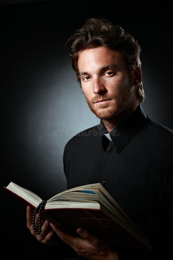 Молодое духовное лицо держа святейшую библию стоковая фотография rf