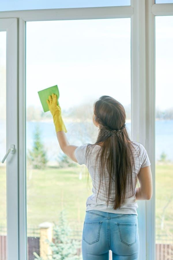 Молодое женское обтирая окно стоковые фото