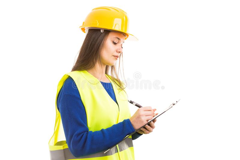 Молодое женское сочинительство инженера на доске сзажимом для бумаги стоковое изображение