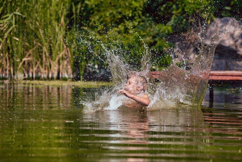 Молодое заплывание мальчика на лете стоковое изображение rf