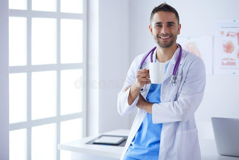 Молодое и уверенное мужское положение портрета доктора в медицинском офисе стоковые изображения