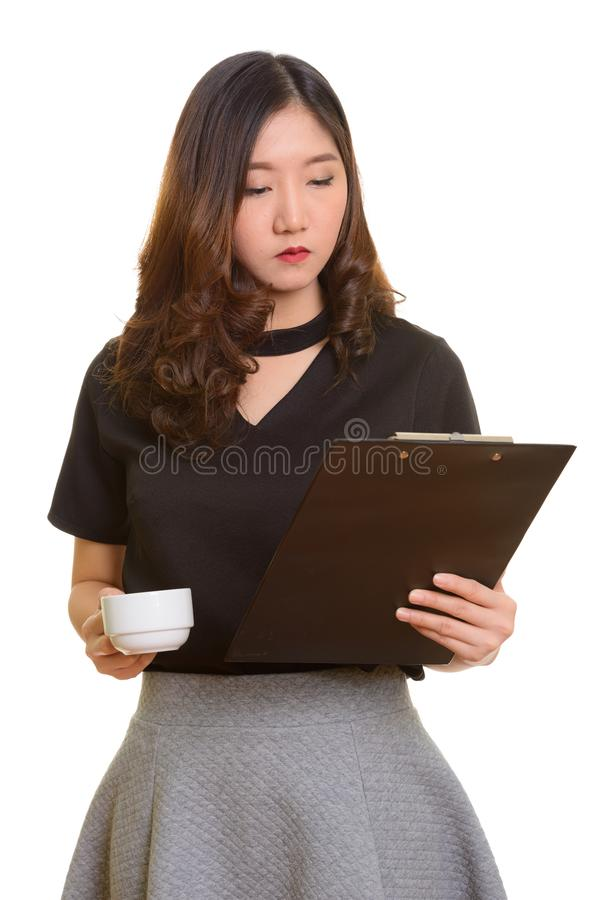 Молодое красивое азиатское владение промежутка времени доски сзажимом для бумаги чтения коммерсантки стоковые изображения rf