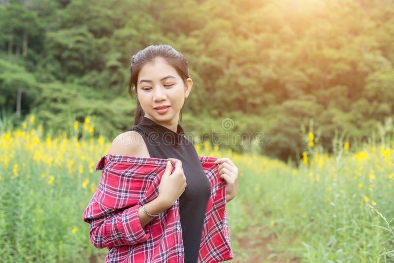 Молодое красивое положение женщины в наслаждении поля цветка стоковая фотография rf