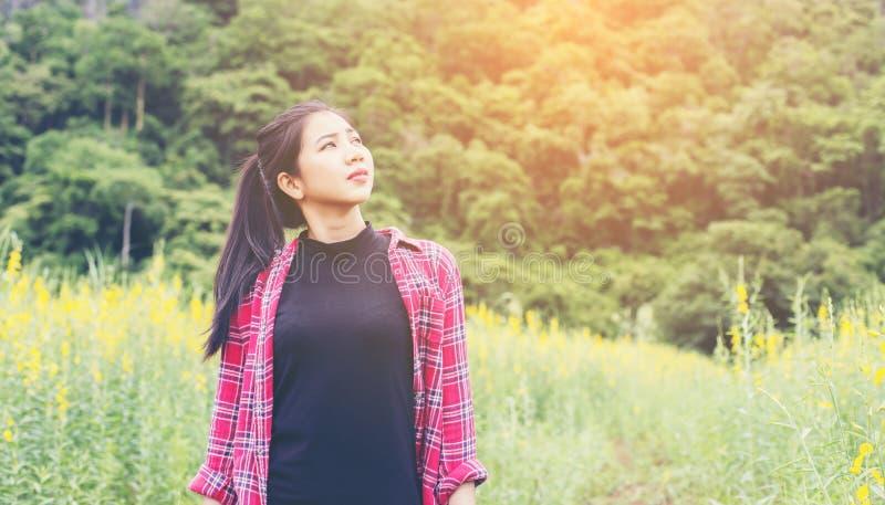 Молодое красивое положение женщины в наслаждении поля цветка стоковые изображения rf