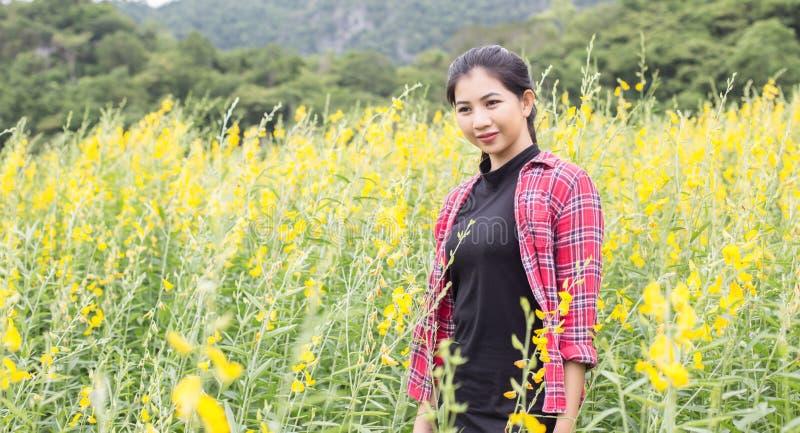 Молодое красивое положение женщины в наслаждении поля цветка стоковое изображение