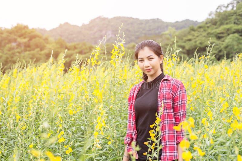 Молодое красивое положение женщины в наслаждении поля цветка стоковое фото