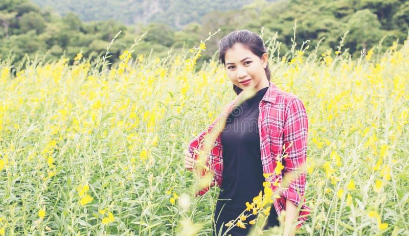 Молодое красивое положение женщины в наслаждении поля цветка стоковая фотография