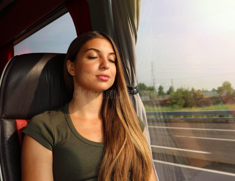 Молодое красивое усаживание спать женщины в автобусе Пассажир автобуса путешествуя усаживание в месте и спать стоковые изображения