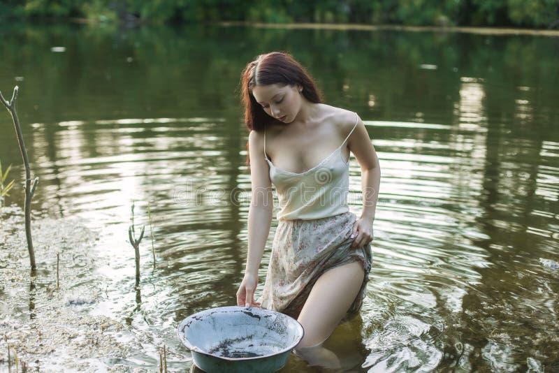 Молодое крестьянское положение женщины в озере стоковое изображение rf