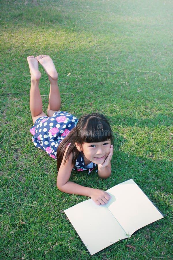 Молодое маленькое азиатское чтение девушки в парке стоковые изображения
