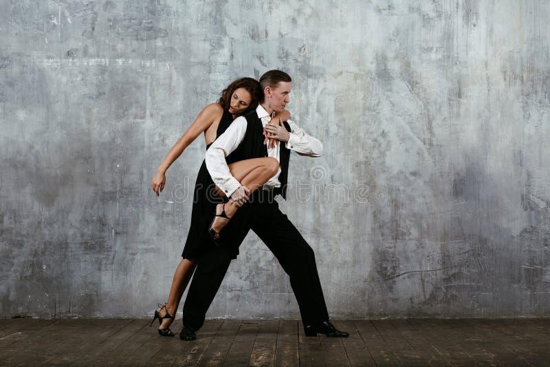 Молодое милое танго танца женщины и человека стоковая фотография