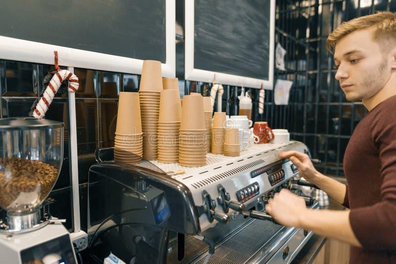 Молодое мужское barista делает напиток около машины кофе Концепция дела кофейни стоковые фото