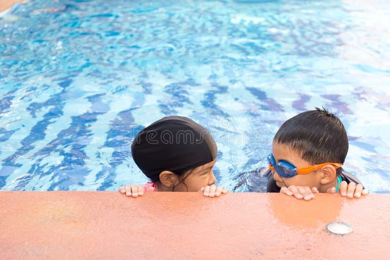 Молодое плавание мальчика и девушки в бассейне стоковая фотография rf