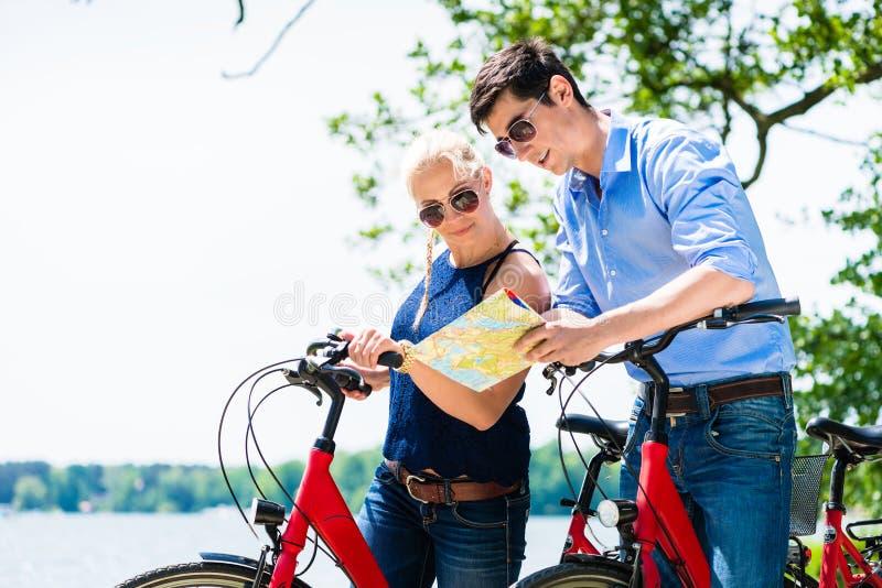 Молодое положение пар с велосипедом смотря карту стоковые фотографии rf