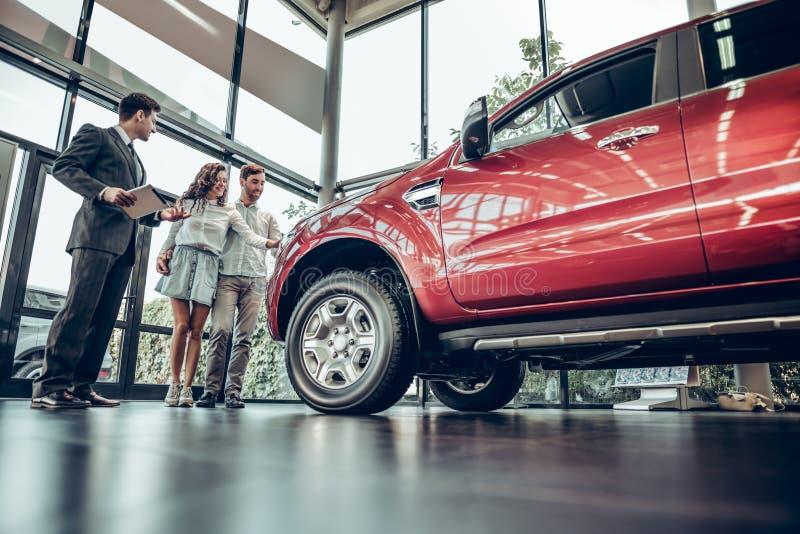Молодое положение продавца автомобилей на дилерских полномочиях говоря об особенностях автомобиля к клиентам стоковые изображения rf