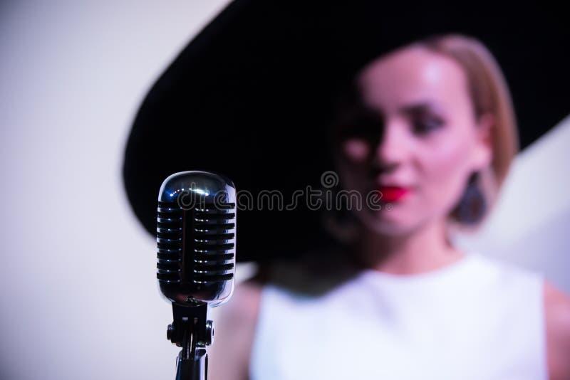 Молодое привлекательное положение женщины около mic на предпосылке белой стены в большой шляпе Mic в фокусе стоковое изображение rf