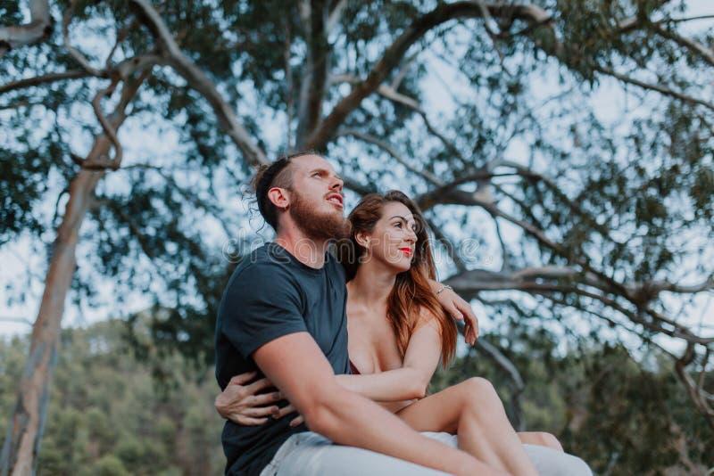 Молодое реальное усаживание пар и обнимать пока смотрящ природу стоковая фотография