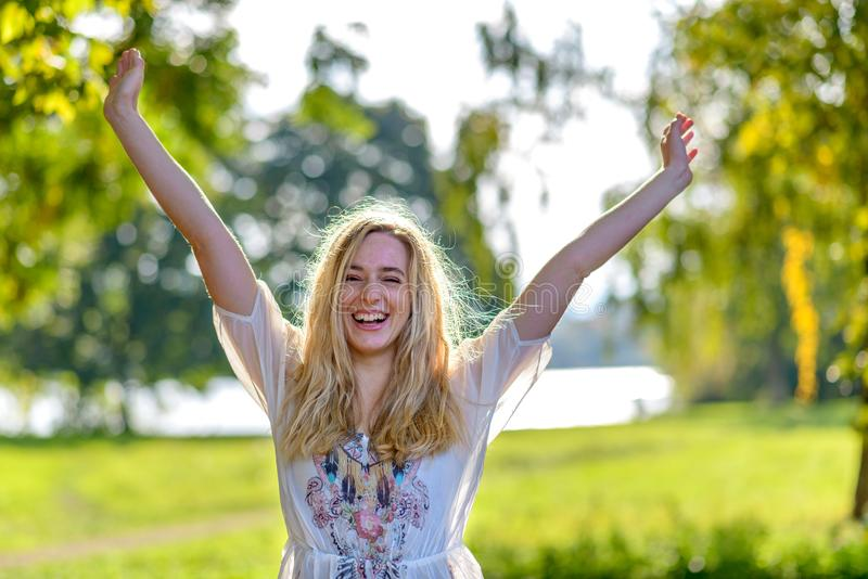 Молодое счастливое повышение женщины вручает outdoors стоковое фото
