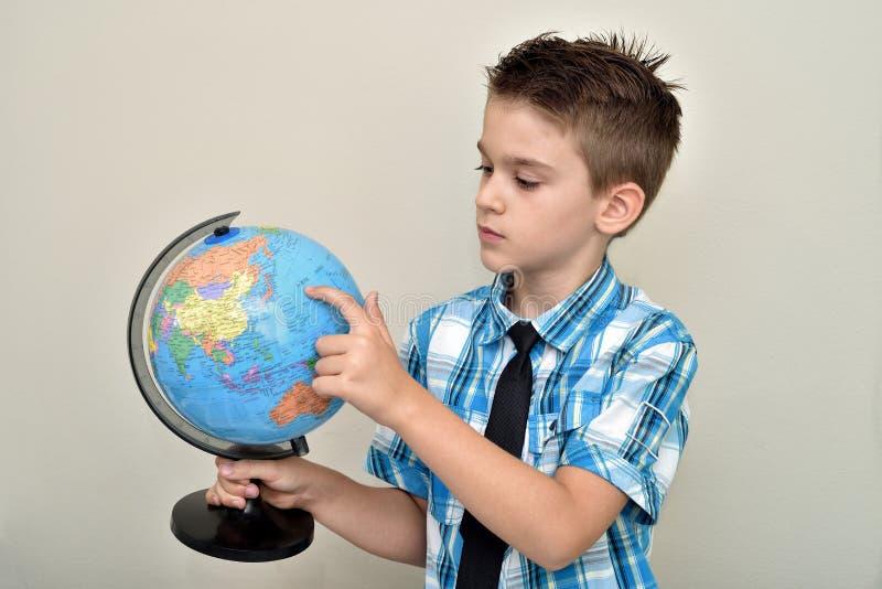 Молодое удерживание мальчика и рассматривать глобус стоковое фото