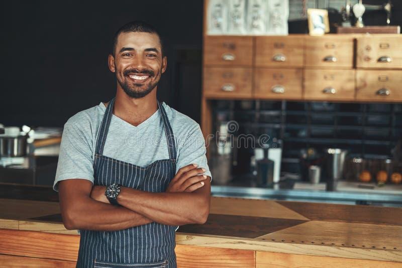 Молодое усмехаясь barista представляя около счетчика на его кафе стоковое изображение rf