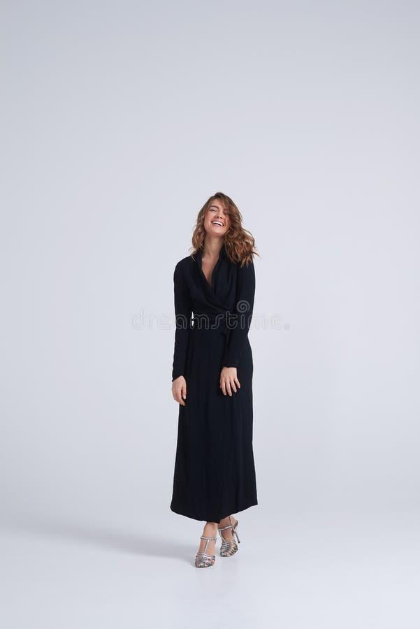 Молодое шикарное брюнет нося длинное черное платье смотря пришло стоковые фото