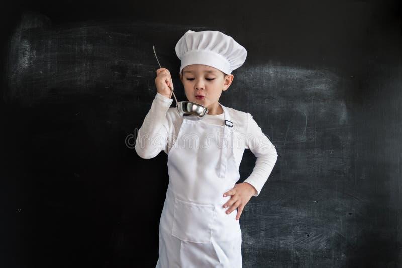 Молодое ` s мальчика стоя близко классн классный проверяя суп Молодой мальчик шеф-повара Творческая идея проекта для календаря 20 стоковое изображение rf