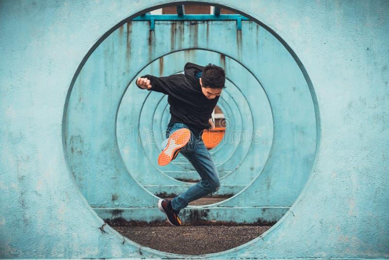 Молодой азиатский активный скакать человека и пиная действие, предпосылка стены круга закрепляя петлей Весьма концепция деятельно стоковые фото