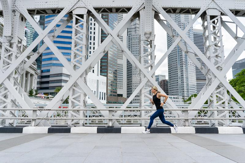Молодой азиатский бегун женщины бежать на дороге моста города стоковая фотография rf