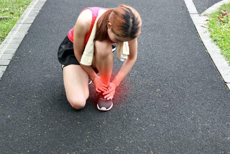 Молодой азиатский бегун женщины фитнеса страдая от сломленной переплетенной лодыжки Идущая концепция аварии ушиба стоковое фото