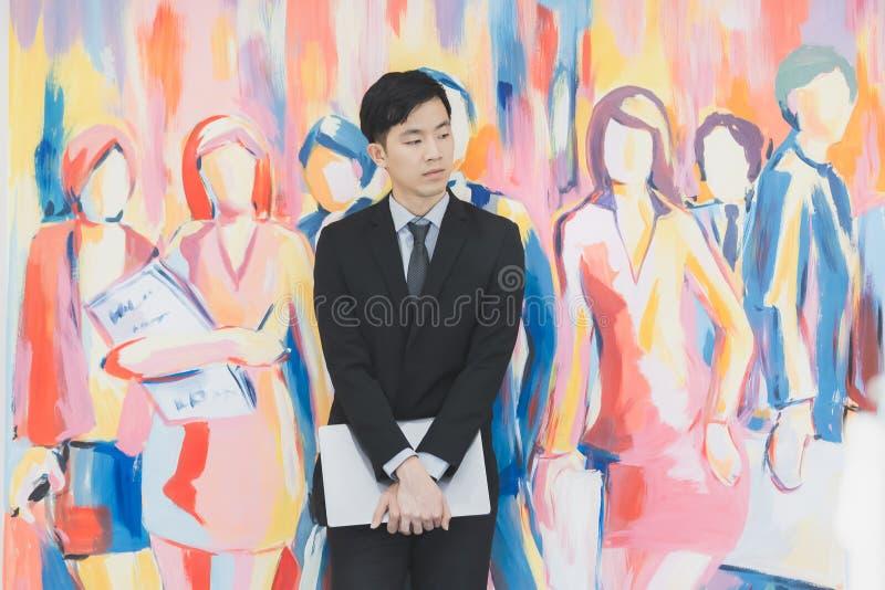Молодой азиатский бизнесмен в черном положении костюма стоковая фотография rf
