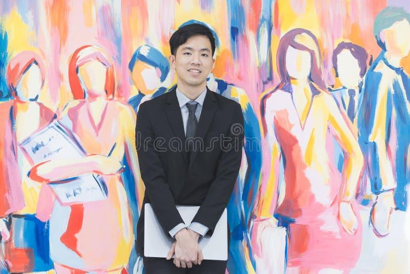 Молодой азиатский бизнесмен в черном положении костюма стоковые изображения