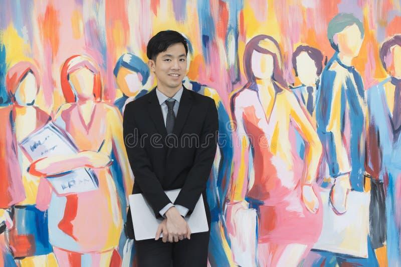 Молодой азиатский бизнесмен в черном положении костюма стоковые фото