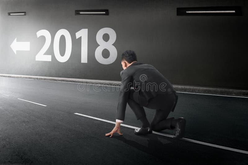 Молодой азиатский бизнесмен готовый для того чтобы побежать с 2018 номерами стоковые изображения rf