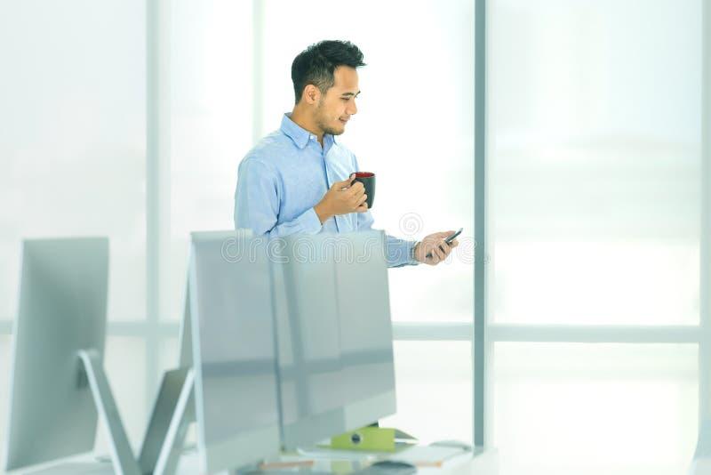 Молодой азиатский бизнесмен держа кофейную чашку и смотря smatph стоковые изображения